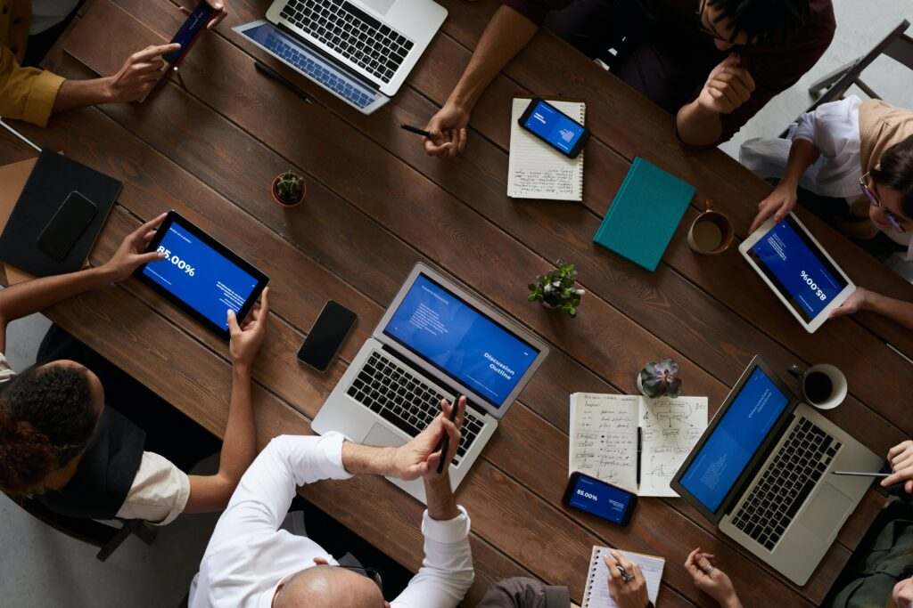 A group sits around a conference table with laptops and tablets